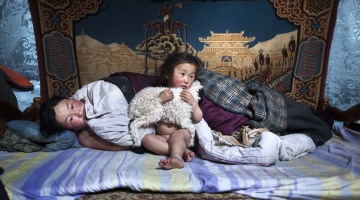 © Alessandro Grassani - Asia, Mongolia. Erdene Tuya together with her 3 years old son called Tuvchinj (he hugs a young sheep which sleeps with them) just wake up.