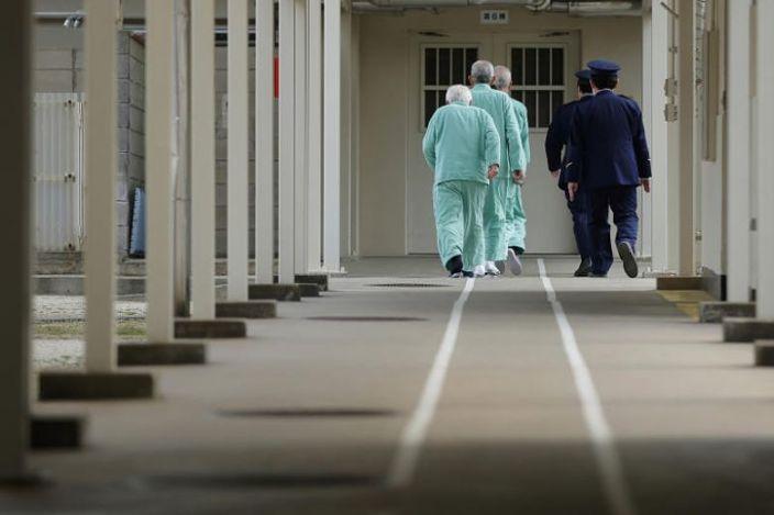 Anziani giapponesi in carcere in fila per tornare in cella, scortati dalla polizia